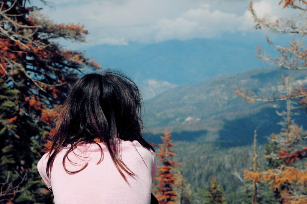 Eine Frau schaut in ein Tal voller Bäume.