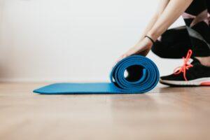 Bewegungsübungen daheim: Eine Frau rollt ihre Fitness-Matte aus
