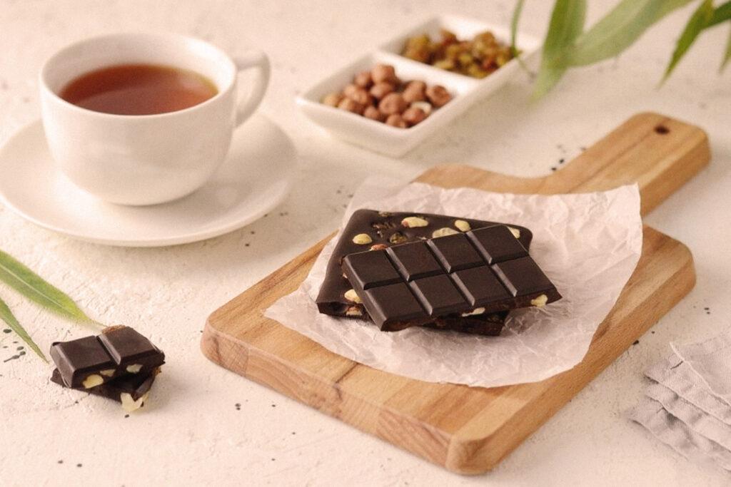 Eine Tasse Tee und Schokolade mit Nüssen kann Glückshormone freisetzen.