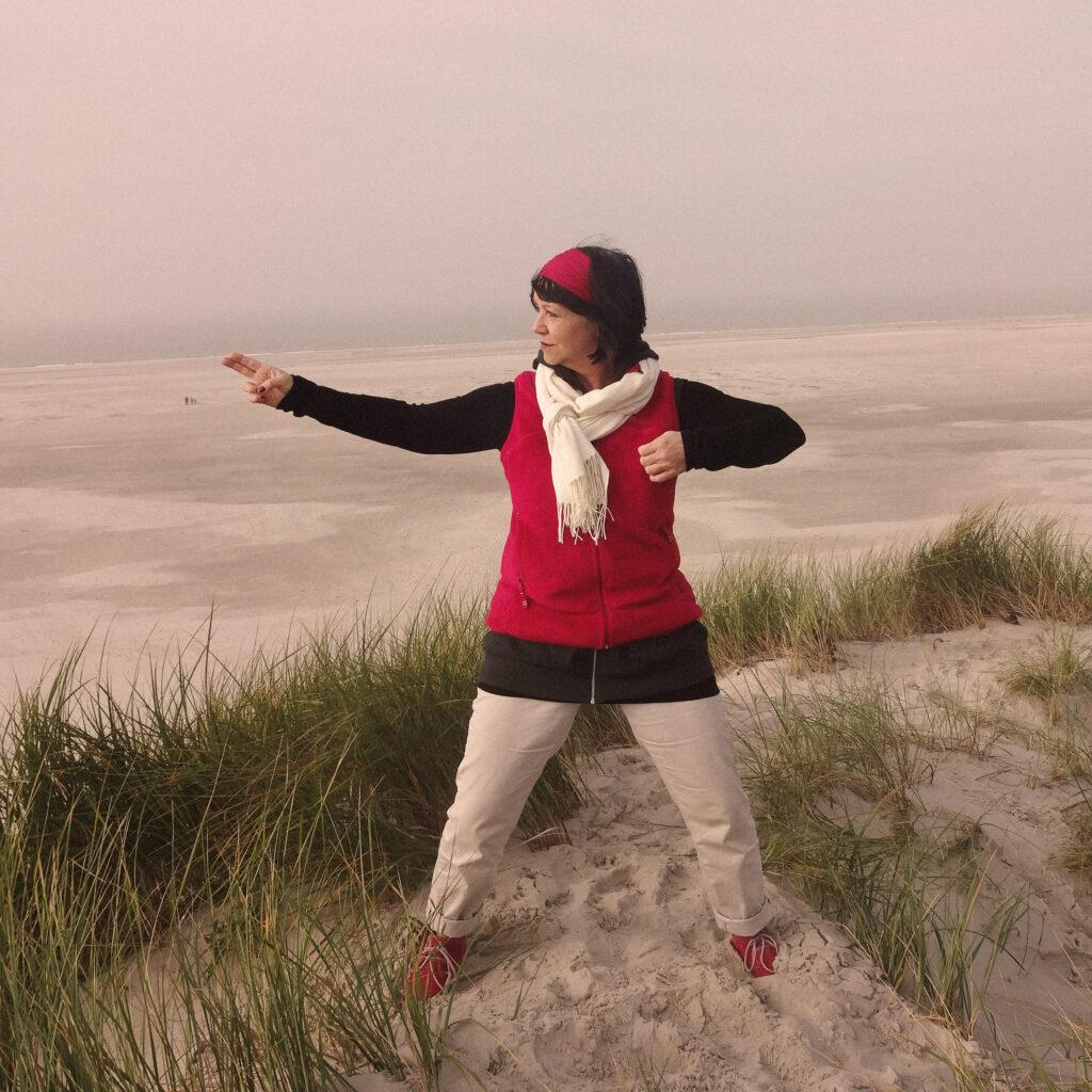 Eine Frau führt in den Dünen stehend eien Qi Gong Übung aus
