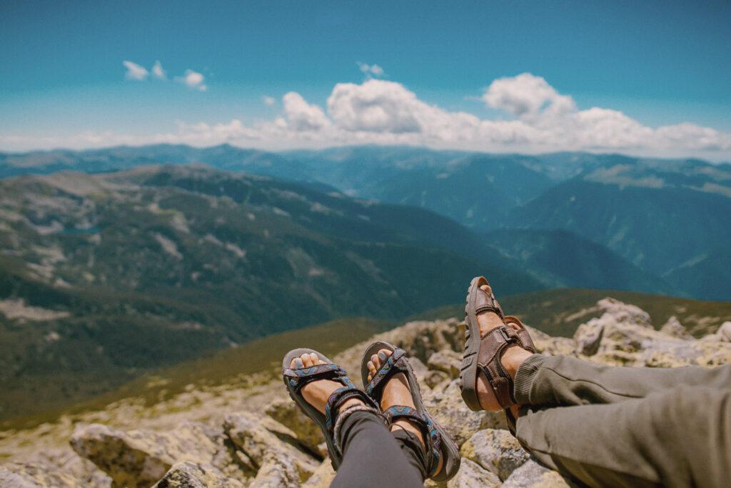 2 Menschen machen Pause auf einem Berg und blicken ins Tal