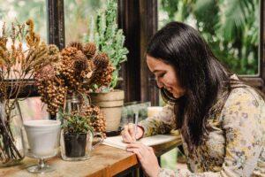 Frau schreibt Tagebuch und lacht