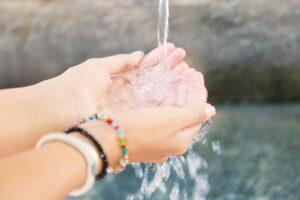 Eine Frau hält Wasser in der Hand Hydrotherapie