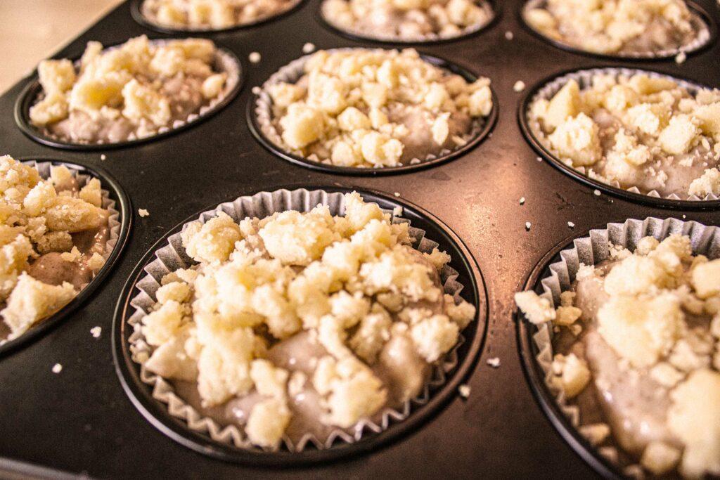 Vegane Apfelmuffins und Zimtstreusel in der Form, ungebacken
