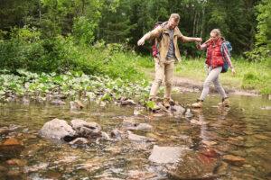 Zwei Menschen überqueren einen Waldbach