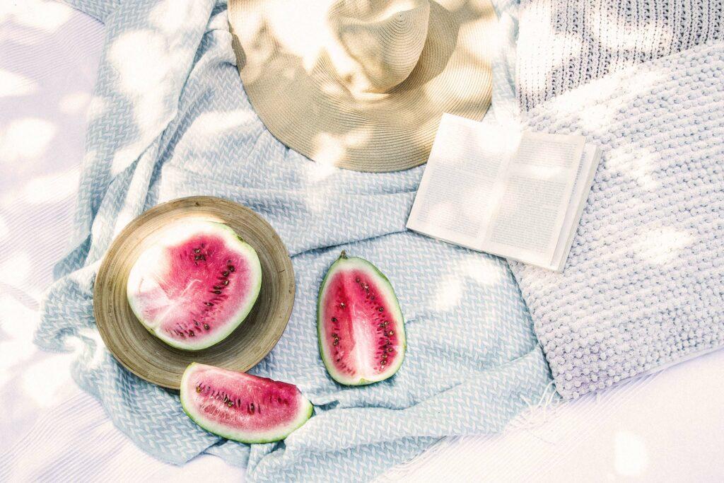 7 kühlenede Lebensmittel im Sommer – ein Picknick im Park mit Wassermelone, Buch und Hut